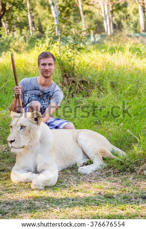 Young man sitting with a white lion in Casela world of adventures park on Mauritius