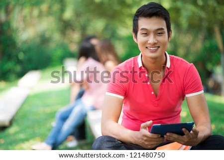 Young man sitting with digital tablet outdoors - stock photo