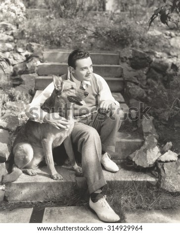 Young man sitting with dog on steps outdoors - stock photo