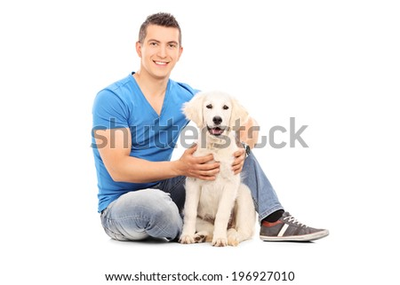 Young man sitting with his dog on the floor isolated on white background - stock photo