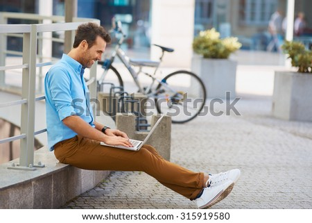 Young man sitting with laptop outside the office - stock photo