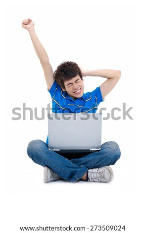 Young man sitting with laptop with his arms up