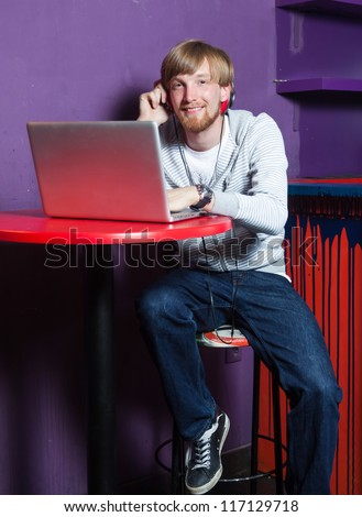 Young man sitting working on laptop in cool location