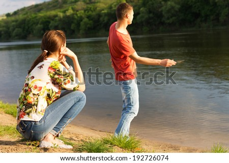 Young man skimming stones across the water of a tranquil mountain lake watched by his young girlfriend sitting in the sunshine on her haunches - stock photo