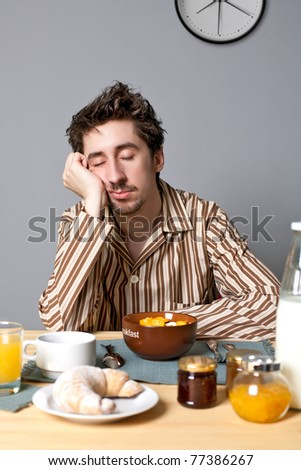 Young man sleeping at breakfast table - stock photo