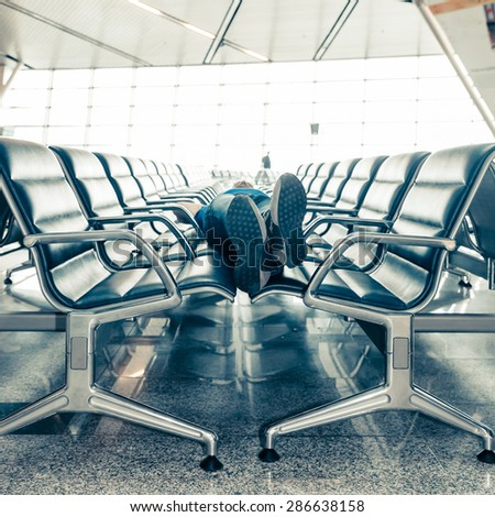 Young man sleeping at the airport while waiting for delayed flights - stock photo