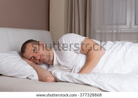 Young man sleeping in a bed - stock photo