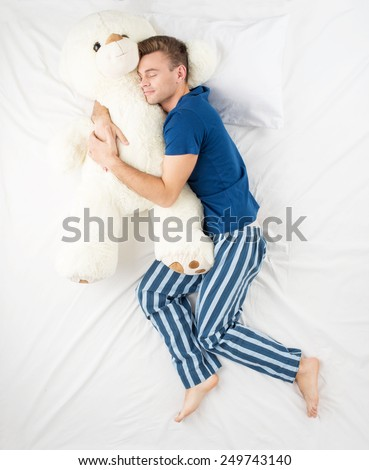 Young man sleeping in an embrace with a large white teddy bear. Top view photo - stock photo