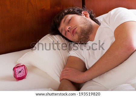 Young man sleeping in bed in the morning - stock photo