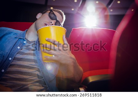 Young man sleeping in chair at the cinema - stock photo
