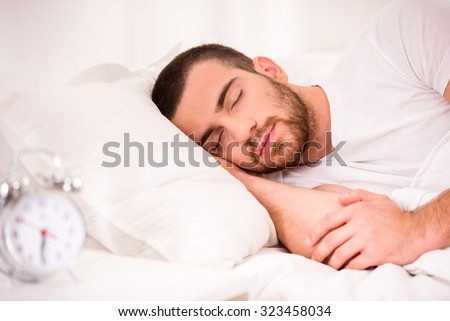 Young man sleeping in comfortable bed at home. - stock photo