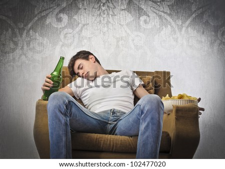 Young man sleeping on an armchair while holding a beer bottle and a bowl of chips - stock photo