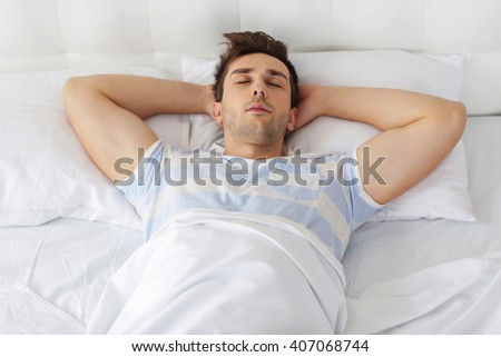 Young man sleeping on comfortable bed - stock photo