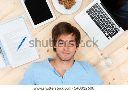 young man sleeping on the floor with laptop - stock photo