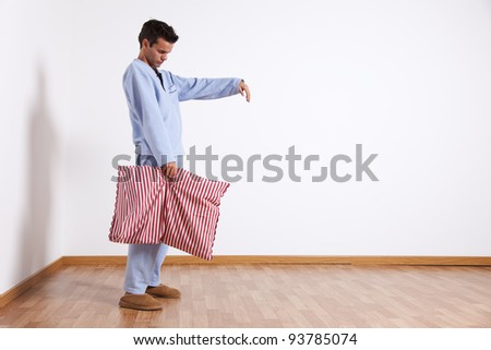 Young man sleepwalking at his home dress with nightclothes (isolated on white) - stock photo