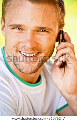 Young man smiles and speaks on phone, close up.
