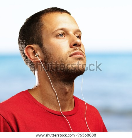 young man smiling and listening to music with a sea as a background - stock photo