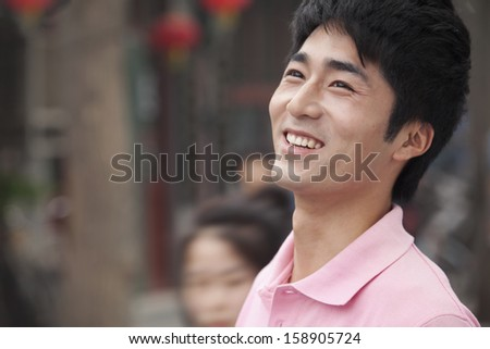 Young man smiling and looking away - stock photo