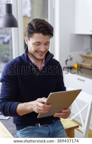 Young man smiling as he surfs the internet on his tablet computer while sitting perched on the edge of a kitchen table