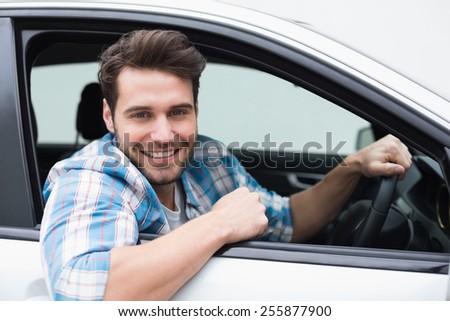 Young man smiling at camera in his car - stock photo