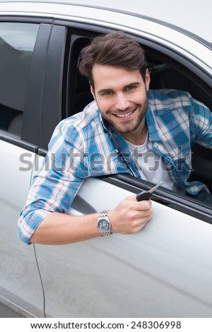 Young man smiling at camera showing key in his car - stock photo