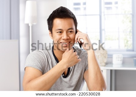 Young man smiling happy, talking on mobilephone, smiling, looking away. - stock photo