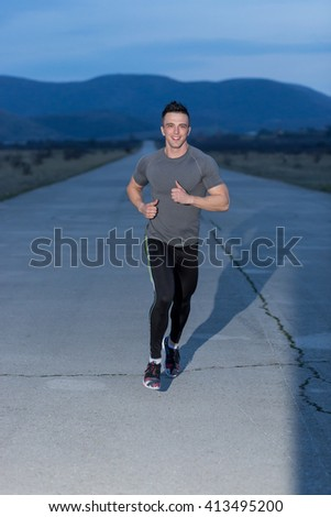 Young man smiling in sportswear posing in the street smiling, runner resting in street night. active lifestyle - stock photo