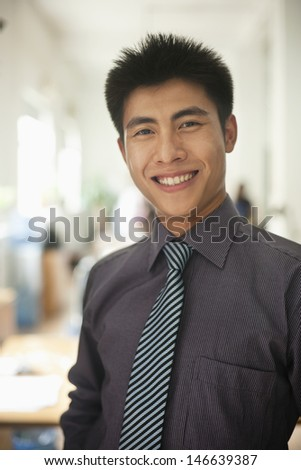 Young man smiling in the office, portrait