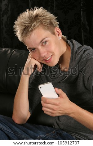 Young man smiling leaning on his elbow holding a mobile device