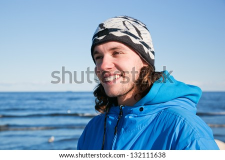 Young man smiling portrait on the beach in a sunny cold day