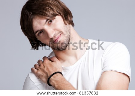 young man smiling, studio shot - stock photo