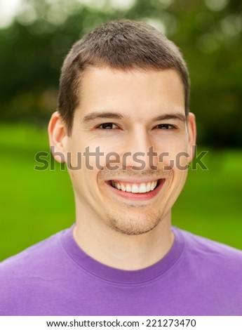 Young man smiling. Vibrant green background.