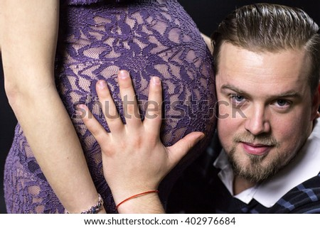 Young man smiling while listening to pregnant womans stomach