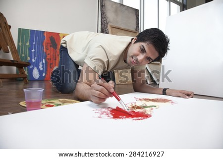 Young man smiling while painting on a large canvas at an art studio