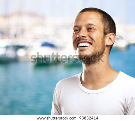 young man smiling with a harbor as a background