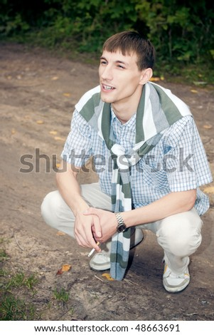 young man smoke cigarette in the squatting position