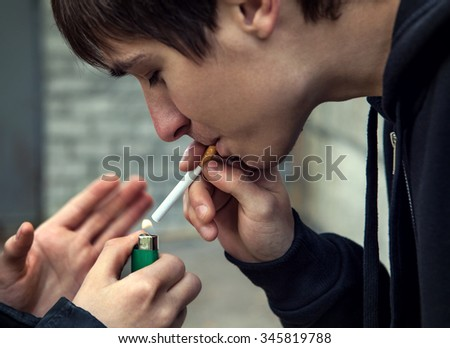 Young Man smoke the Cigarette on the Street