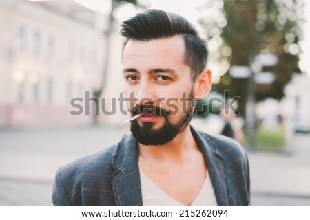 young man smokes a cigarette on the street
