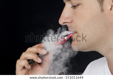 Young man smoking an electronic cigarette. Black background. - stock photo