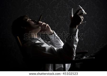 young man smoking cigar and drinking cognac at night - stock photo