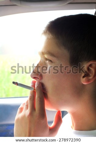 Young Man smoking Cigarette in the Car