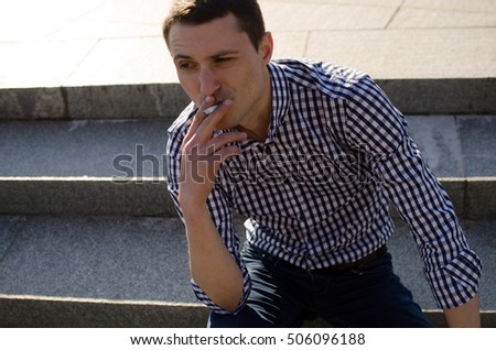 Young man smoking cigarette on the street