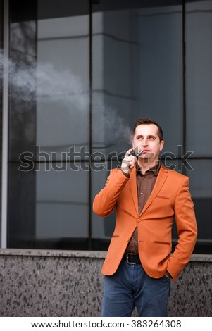 Young man smoking electronic cigarette on background of building.