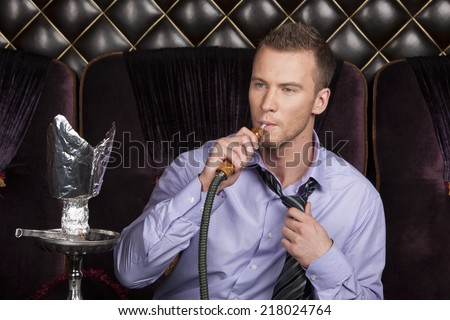 Young man smoking shisha in restaurant. man resting with hookah at shisha house  - stock photo