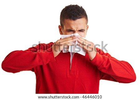 Young man sneezing in a paper handkerchief