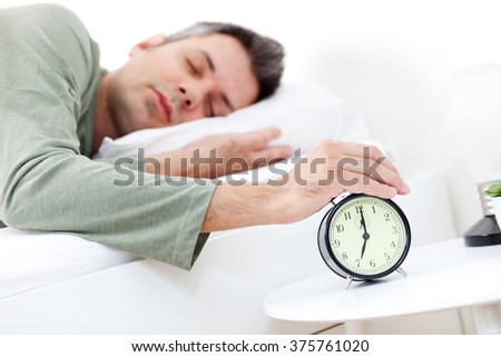 Young man snoozing alarm clock in the early morning, shallow depth of field, focus on foreground - stock photo
