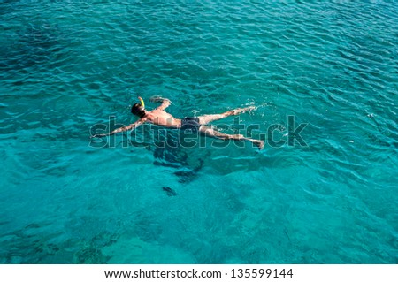 Young man snorkeling in blue sea - stock photo