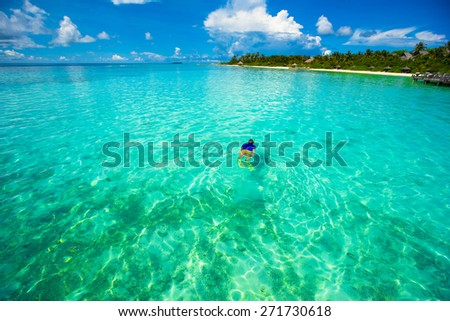 Young man snorkeling in clear tropical turquoise waters - stock photo