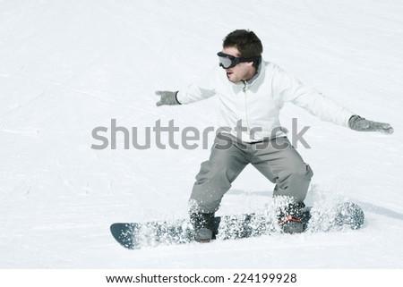 Young man snowboarding, action shot, full length - stock photo