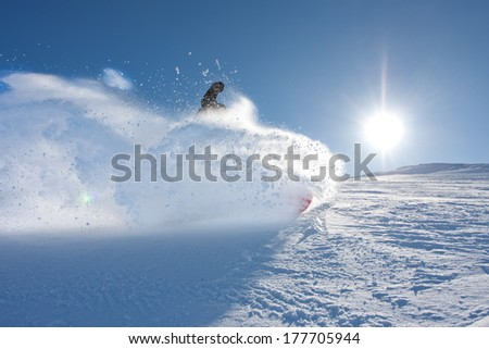 Young man snowboarding in sunshine and perfect weather